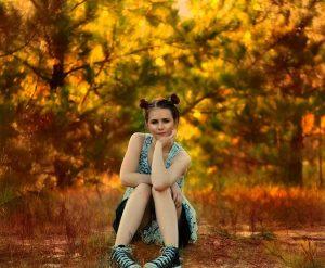 Chica adolescente sentada en el suelo de un parque en otoño