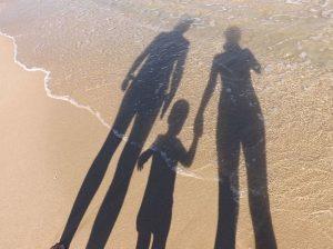 Sombra de dos adultos tomando de la mano a un niño en la orilla de la playa