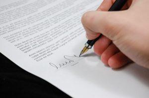 Mano firmando contrado con una pluma